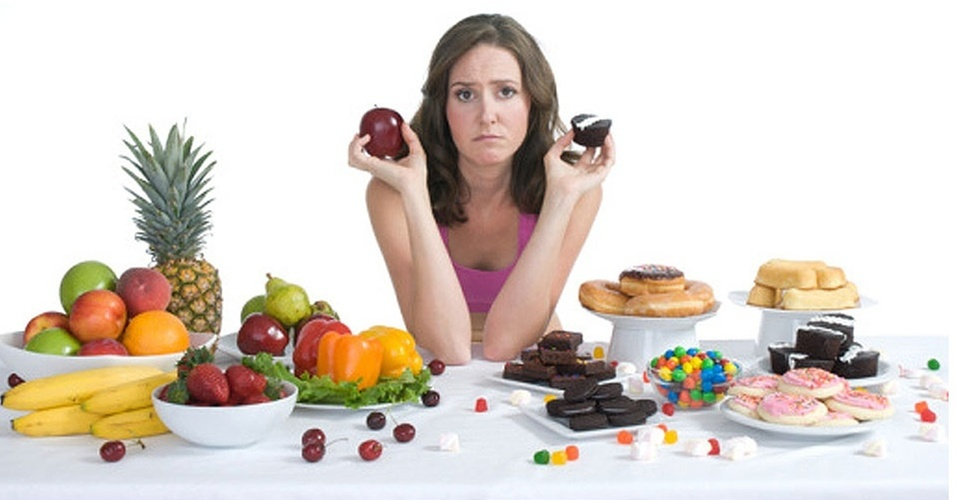 mulher-entre-doces-e-frutas-e-legumes-dieta-1303740905987_956x500
